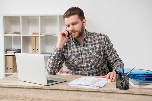 mężczyzna w koszuli w kratę siedzi przy biurku i wykonuje telefon