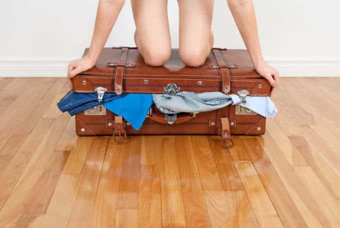Kobieta próbuje zamknąć walizkę z ubraniami