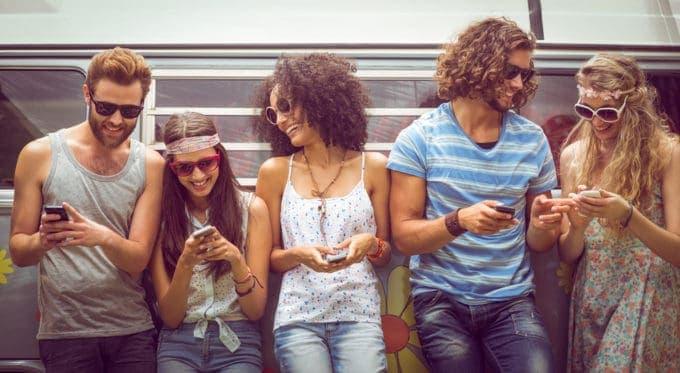Grupa ludzi oparta o samochód bawi się telefonami
