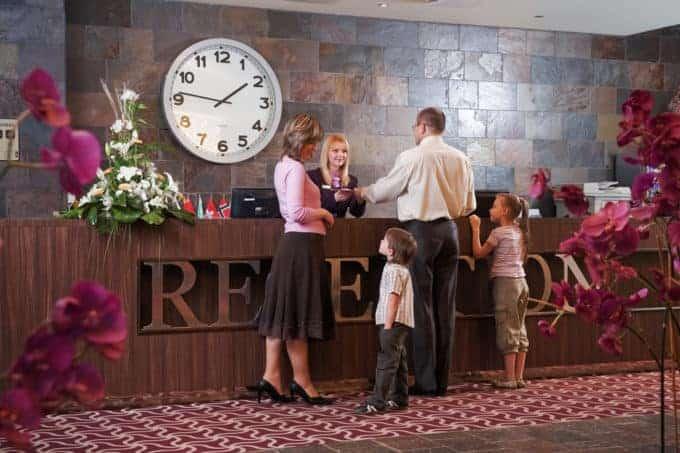 Rodzina odbierająca klucze na recepcji w hotelu