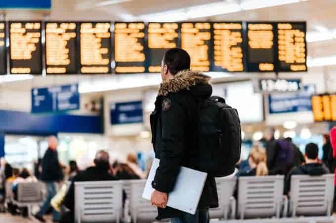 mężczyzna patrzący na tablicę odlotów na lotnisku