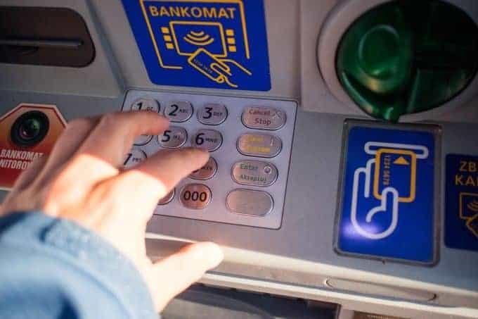 osoba, wybierająca pieniądze zbankomatu