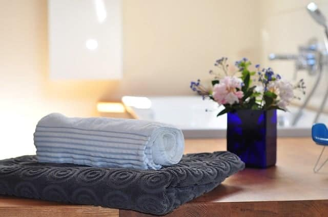 ręczniki i wazonik ułożone na półce w łazience
