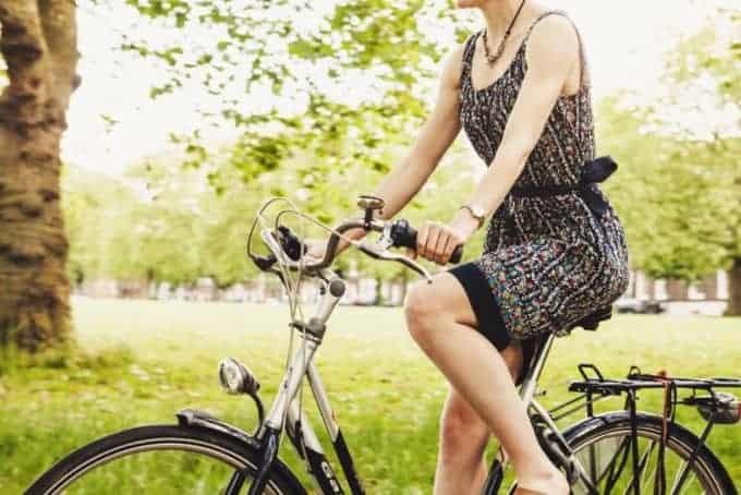 kobieta jedzie na rowerze przez park