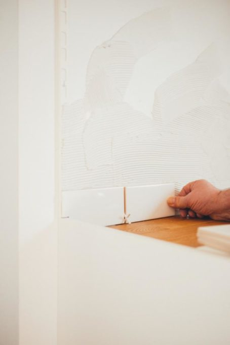osoba kładzie płytki na ścianie