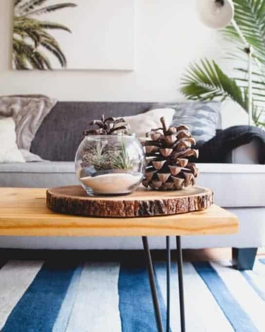 drewniany stolik, na którym leży wazon i szyszki