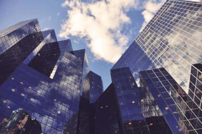 wysokie budynki, wktórychodbija się błękitne niebo