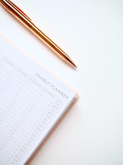Na stole leżą planer oraz długopis