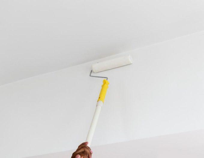 mężczyzna maluje ściany na biało