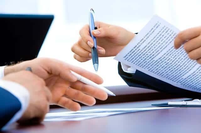 kobieta podaje mężczyźnie długopis do podpisania dokumentu