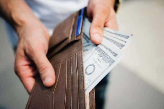 Mężczyzna trzyma portfel iwyciąga zniego gotówkę