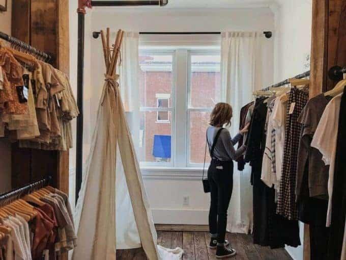 dziewczyna przeglądająca ubrania na wieszakach w sklepie